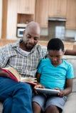 生阅读书,当坐在他旁边的儿子使用数字式片剂时 库存照片