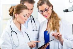 年轻医生队诊所的与片剂计算机 库存照片