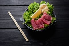 生鱼片一个五颜六色的盛肉盘与鱼的在板材用沙拉、山葵和姜 免版税库存图片