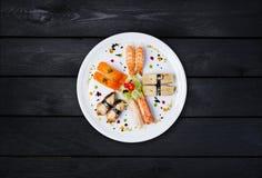 生鱼片在一块白色圆的板材设置了,装饰用小花,日本食物,顶视图 黑色木背景 库存图片