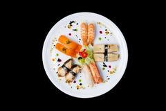 生鱼片在一块白色圆的板材设置了,装饰用小花,日本食物 顶视图 隔绝在黑色 图库摄影