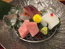 生鱼片集合特写镜头服务与在银器板材和冰围拢的山葵 库存照片