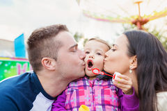生,亲吻他们的女儿吹的泡影,娱乐的母亲 免版税库存照片