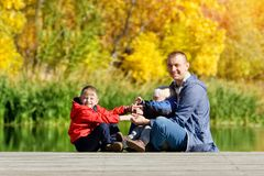 生,并且两个儿子在船坞使用 秋天,晴朗 侧视图 免版税库存照片