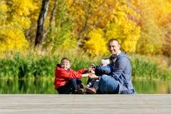 生,并且两个儿子在船坞使用 秋天,晴朗 侧视图 库存照片