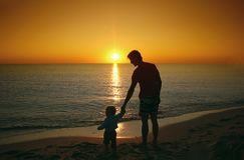 生,并且他的小小儿子在日落海滩一起聚集 Fa 免版税库存照片