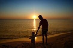 生,并且他的小小儿子在日落海滩一起聚集 Fa 图库摄影
