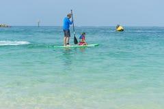 生,并且坐他可爱的矮小的女儿站立委员会获得乐趣在夏天海滩假期时 免版税图库摄影