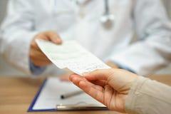 医生给一张处方一名女性患者 图库摄影