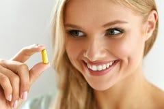 维生素和补充 拿着鱼油胶囊的美丽的妇女 库存图片