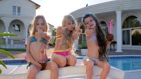 生活损坏了孩子,在摆在为照相机的水池附近的富有的孩子,儿童名人暑假,孩子集会 影视素材