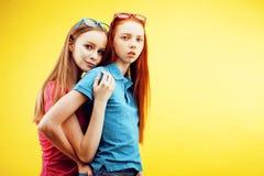 生活方式人概念:有两个相当年轻学校的十几岁的女孩乐趣愉快微笑在黄色背景 库存照片