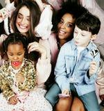 生活方式和人概念:用庆祝在诞生天的不同的年龄孩子的年轻俏丽的变化国家妇女 图库摄影