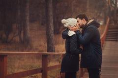 生活方式捕获愉快夫妇亲吻室外在舒适在森林里温暖步行 免版税库存照片