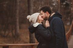 生活方式捕获愉快夫妇亲吻室外在舒适在森林里温暖步行 图库摄影