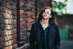 生活方式深色的女孩时尚画象岩石黑色样式的,站立户外在城市街道 免版税图库摄影