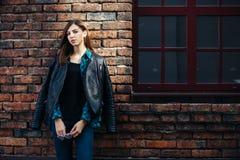 生活方式深色的女孩时尚画象岩石黑色样式的,站立户外在城市街道 图库摄影