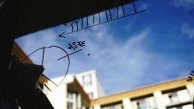 生活方式:从玻璃的美好的少妇清洁算术企业图表与蓝天,背景的摩天大楼 股票录像