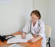 医生治疗师填写运作的杂志,坐 免版税库存图片