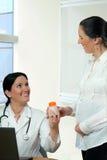给维生素的微笑的医生一名孕妇 库存图片