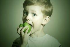 维生素 苹果儿童吃 小滑稽的男孩用绿色苹果 背景玉米片食物健康宏观工作室白色 果子 免版税图库摄影