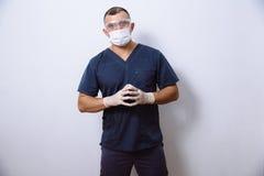 年轻医生画象有面具的在白色背景 概念手术和健康 库存图片