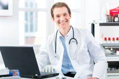 年轻医生画象诊所的在膝上型计算机 库存图片