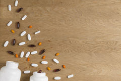维生素,膳食补充剂,药物,在木桌上的片剂pils与两个开放白色瓶 药房,医学和 图库摄影