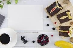 生` s与白纸、甜早餐从tosts,莓果和咖啡的天背景 与白色木的特写镜头 库存图片