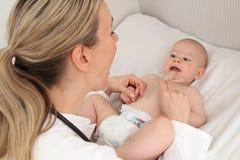 医生examinate有小铲的一个婴孩 库存图片