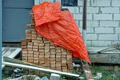 用一块红色油布盖的堆棕色砖对房子的墙壁 库存图片