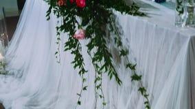 用一插花装饰的新婚佳偶主席团,与在花瓶和曲拱的蜡烛,迪斯科光运作 影视素材