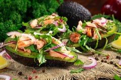 用三文鱼、红洋葱和芝麻菜充塞的鲕梨小船 概念健康食物 图库摄影