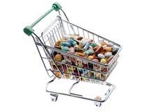 用不同的五颜六色的药片的商店推车在白色 免版税库存照片