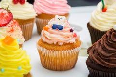 用不同的口味的五颜六色的杯形蛋糕 杯形蛋糕装饰的糖果熊 beautifull在白色桌结块 关闭 免版税库存图片