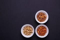 用不同的坚果的三个碗在一张黑桌上 库存图片