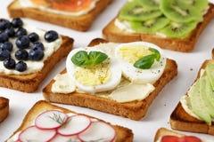 用不同的多士的三明治用鸡蛋和hummus在白色桌上 库存照片