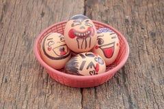 用不同的字符的鸡蛋在篮子 免版税库存照片