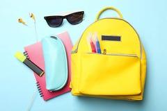 用不同的学校用品和辅助部件的黄色背包 免版税库存照片