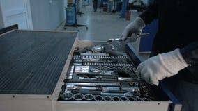 用不同的工具的技工开放蓝色金属箱子为在现代服务站的汽车修理 影视素材