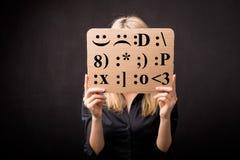 用不同的情感emojis的纸板在面孔前面 免版税图库摄影