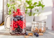 用不同的新鲜的夏天莓果的一个玻璃瓶子在桌上 免版税库存照片