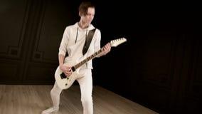 用不同的眼睛的时髦的节奏吉他弹奏者在传神播放白色的黑背景的白色衣裳 影视素材