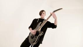 用不同的眼睛的时髦的节奏吉他弹奏者在传神播放黑色的白色背景的黑色衣服 股票录像