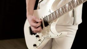 用不同的眼睛的特写镜头时髦的节奏吉他弹奏者在一黑背景传神使用的白色衣裳 股票录像