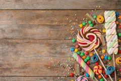 用不同的美味的糖果的平的被放置的文本的构成和空间 免版税库存照片