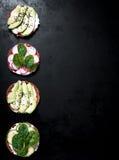 用不同的菜的各种各样的健康素食主义者或素食主义者三明治在黑暗的背景 库存照片