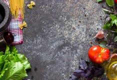 用不同的蕃茄、蓬蒿、意粉、橄榄油、大蒜和木匙子的意大利食物背景 免版税库存照片