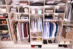用不同的衣裳、家庭材料和鞋子的大衣橱 免版税图库摄影