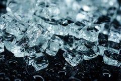 用不同的被击碎的冰块的背景在黑反射桌上用水下降 图库摄影